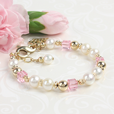 Beautiful gold bracelet for babies and children with white cultured pearls and pink crystals. Shown with extension chain and charm.