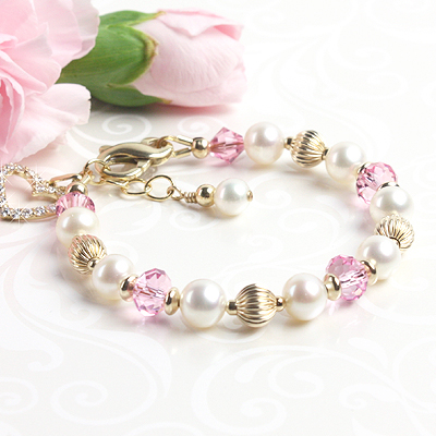 Gold baby and child bracelet with white cultured pearls and pink sparkling crystal.