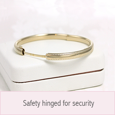 14kt gold filled bangle bracelet with engraved floral pattern and safety clasp for security.