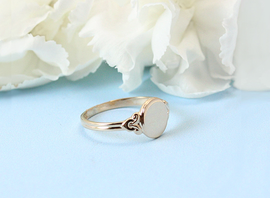 Girls gorgeous 10kt gold oval signet ring with designed border.