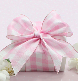 Wrapped baby gift in white with pink bow.