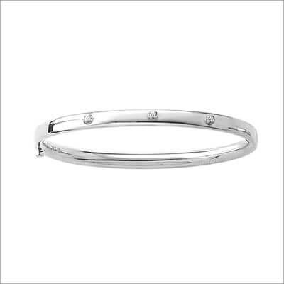 Silver bangle bracelet for children set with 3 genuine diamonds; safety hinged.