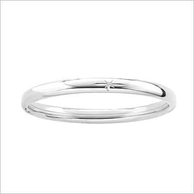 Childrens silver bangle bracelet set with a genuine diamond; safety hinged.