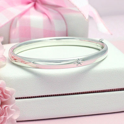 Polished silver bangle bracelet with a genuine diamond. Safety clasp. Child size 5.25 in.